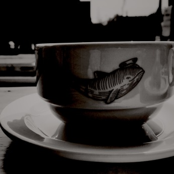 black and white photo of a coffee mug showing the logo that is a dolphin