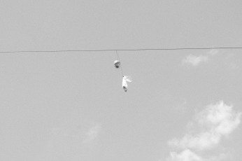 Black and white version of a doll's head hanging on a telephone wire